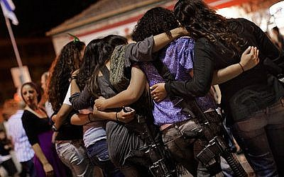 Israeli girls wear automatic rifles as they dance together during a celebration. (Marco Longari/AFP/Getty Images)