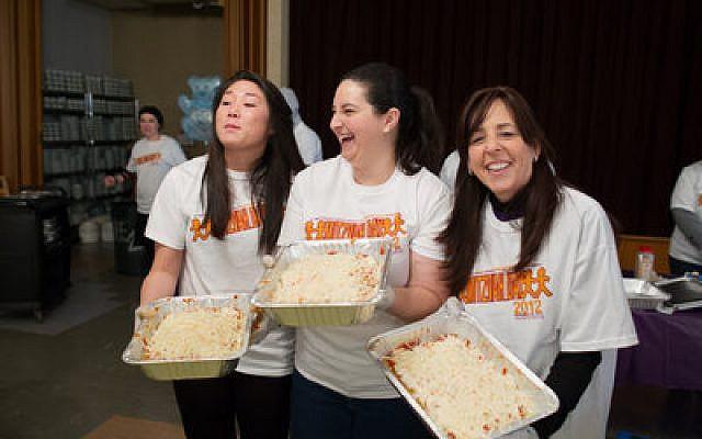 Judy Kanal, right, and two other Mitzvah Day volunteers display kosher lasagna prepared at Shaare Torah. The Volunteer Center coordinated Mitzvah Day. (Josh Franzos photo)
