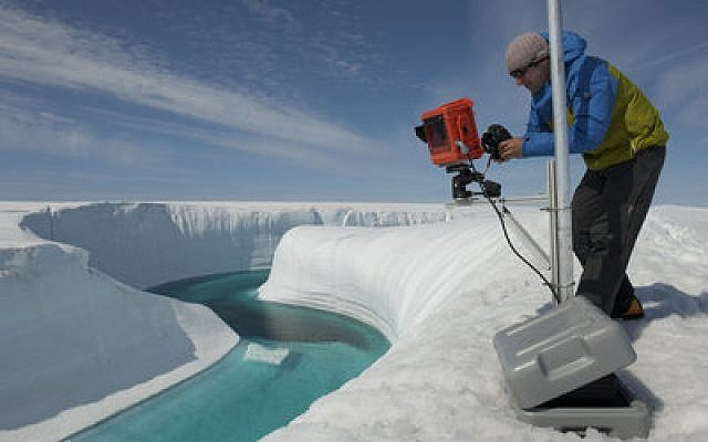 Adam LeWinter installing an EIS time-lapse camera on the edge of a melt channel on the Greenland ice sheet, Greenland. (James Balog, Extreme Ice Survey)