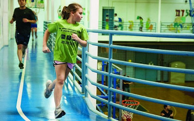 Lily Welch, 10, of Upper St. Clair, reels around the Jewish Community Center track during the Triathlon. (Chronicle photos by Lindsay Dill)