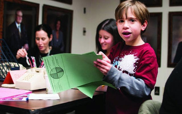Jonah Keller, 8, of Squirrel Hill, collects completed donor sheets from Fundfest volunteers. This is his second year participating in the annual communal fundraising event. (Chronicle photos by Lindsay Dill)