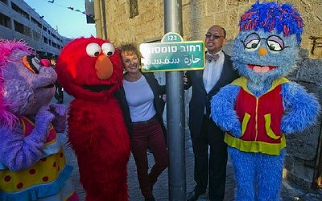 "Avigail, Elmo, Alona Abt (""Rehov Sumsum's"" director on its set in Herzliya), Melvin Ming (president and CEO of Sesame Workshop), and the Arab-Israeli character Mahboub. In the center is the ""Rehov Sumsm"" (""Sesame Street"") sign. (Credit: D Guthrie)"