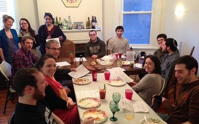 Residents of Moishe House, pictured here with guests and members at a recent Shabbat meal, are preparing for their first Passover seder. (Moishe House photo)