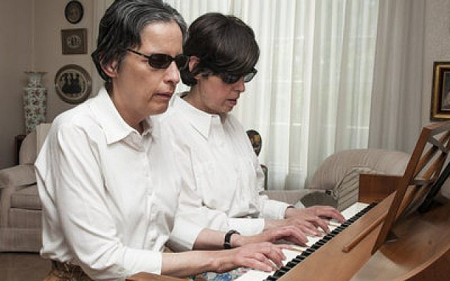 Twin sisters Betty Kane and Judy Meyers play a piano duet in their Squirrel Hill home. Despite the twins' blindness since birth, they've become accomplished pianists, and they often volunteer their musical services at community events. (Chronicle photo by Lindsay Dill)