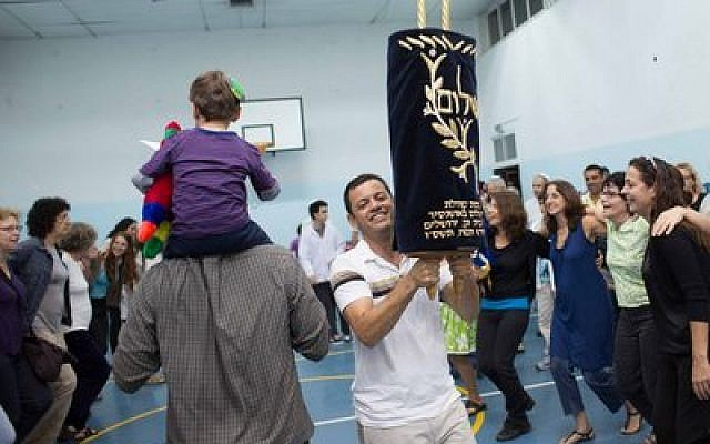 Rabbi Ezra Ende lifts high a Torah during a recent Simchat Torah celebration with members of the Kiryat HaYovel Chavura community in Jerusalem. (Kiryat HaYovel Chavura photo)