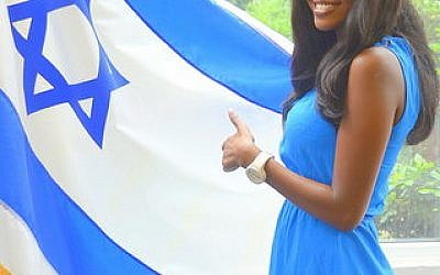 Yitayish Ayenew, the first black Miss Israel and also the first woman of Ethiopian heritage to win the crown, poses with the Israeli flag at Solomon Schechter Day School of Bergen County, N.J., Friday, June 14. (Maxine Dovere photo)
