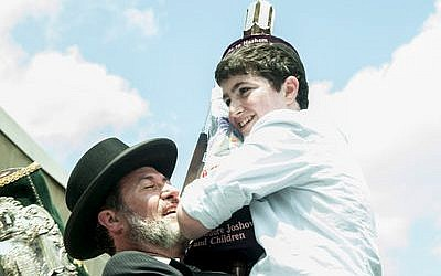 Rabbi Daniel Wasserman raises his son Moshe to dance and celebrate with a new Sefer Torah at Hillel Academy in 2013. The Sefer Torah was dedicated by the Joshowitz family. (Photo by Lindsay Dill)