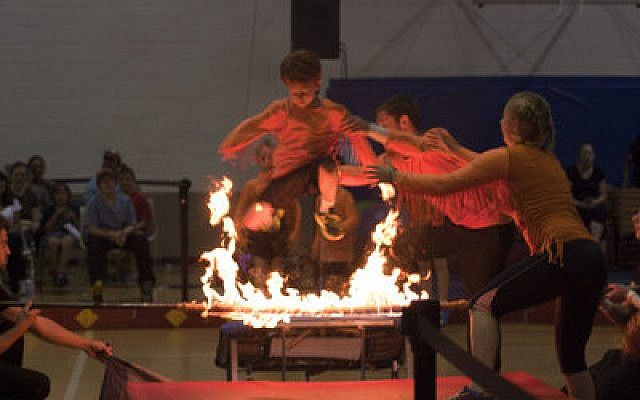 Gabriel Feinstein jumps through a ring of fire during his amazing performance at last week's Circus of the Kids at the Jewish Community Center in Squirrel Hill. He was one of 58 area kids who signed up for the long-running traveling circus, which teaches young people new skills and self-reliance. (Chronicle photos by Ilana Yergin)