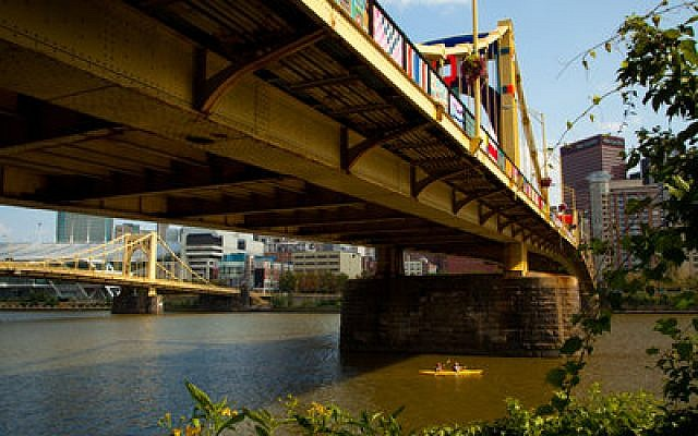 Two kayakers on the Allegheny River get a unique view of the yarn-bombed Andy Warhol Bridge. Thanks to 1,000-plus volunteers, the landmark span is draped in fiber tapestries in a pubic art exhibit that is attracting national attention. (Chronicle photos by Ralph Musthaler)