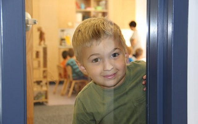 Dominic Morrow looks inquisitively through the window of his classroom at the Jewish Community Center's new Annabelle Rubinstein Early Childhood Development Center, which officially opened this week. (Jewish Community Center of Greater Pittsburgh photo)