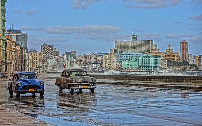 Old American cars are a Cuban staple. Here they drive on a road bordering Havana Bay. (Marla Whitesman/photo illustration)