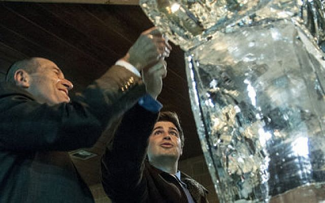 Jay Fingeret and Pittsburgh Councilman Corey O'Connor lit an ice sculpture menorah during last year's IllumiNER ExtraordiNER event, at the Schenley Park ice rink. This year's lifesize candelabra will be made of canned goods for the local food pantry. (Chronicle photo by Lindsay Dill)