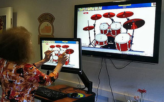 A resident of the LHAS Arbor Unit at Weinberg Village makes music with a virtual set of drums using the unit's new iN2L computer system. The system has proven to be a valuable therapeutic tool while enriching the lives of residents in the Arbor Unit. (JAA photo)