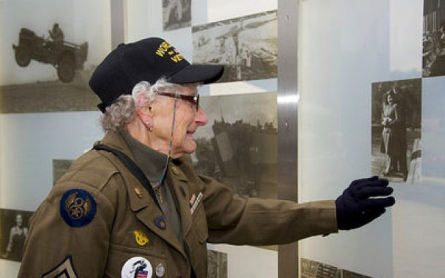 An unidentified woman who served in the Army during World War II studies a photo of her with her husband on the wall of the new World War II memorial on the North Shore. She became overwhelmed with emotion at the sight of the image. (Craig Collins photo)