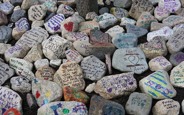 "Above, Circle Campers inscribe rocks with messages to their deceased parents, which they then place in ""memory gardens."" Circle Campers participate in the same kinds of activities as any other camper, including jumping en masse into a lake.  (Photos courtesy of Sandi Lando Welch)"