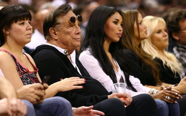 Los Angeles Clippers owner Donald Sterling watches a Clippers game with V. Stiviano (to his left).
