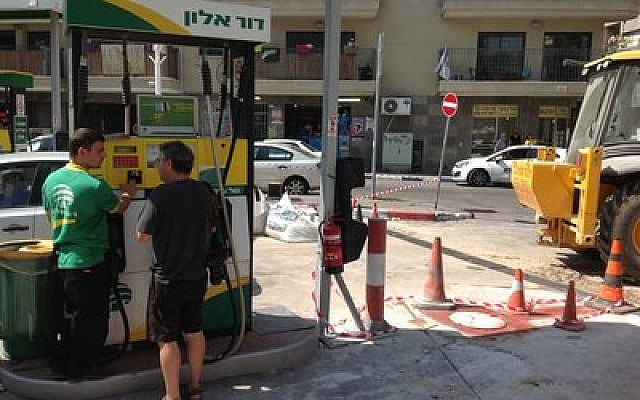 Michael Savlov, left, an attendant at a Tel Aviv gas station, went back to work not long after a shrapnel from a Gaza rocket landed at the site on July 10. (Ben Sales /JTA)