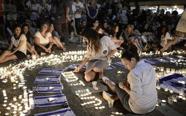 Israelis light candles in Tel Aviv's Rabin Square on Monday as they mourn the news of the death of three abducted Jewish teenagers. Israeli forces found the bodies of the three missing teenagers on Monday after a nearly three-week-long search. (Tomer Neuberg/Flash90)