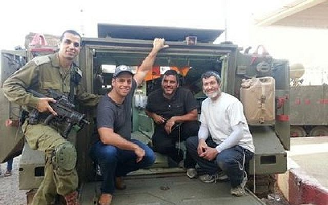 "The ""Pittsburgh Relief Mission"" packed trucks and delivered supplies to the troops in the north on their trip to Israel. Next to the soldier, from left, are Daniel Berkowitz, Daniel Kraut and Rabbi Daniel Wasserman."