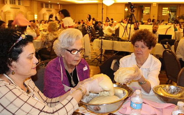 From left:Olga Tkacheva, Marlene Harris and Alice Kuller of Fox Chapel join more than 350 other women and girls as they prepare to separate a portion of challah dough.