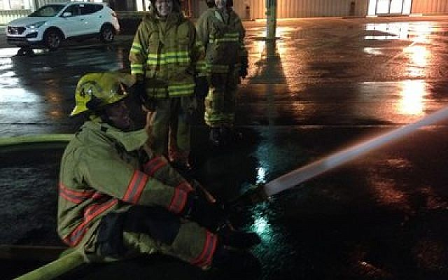 """Citizens Fire Academy participants face 10 weeks of demanding challenges. With 180 gallons of water rushing from a hose every minute, """"you can't let go,""""  said Mt. Lebanon mom, Allison Choder Friedman. (Photo provided by Stacey Reibach)"""