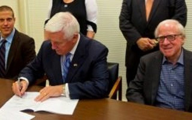 Flanked by Elad Strohmayer, deputy consul general of Israel in Philadelphia, and Len Cooper of the Pennsylvania Jewish Coalition, Gov. Tom Corbett signs into law a bill curtailing the potential business dealings of corporations that invest in Iran. (Photo provided by Pennsylvania Jewish Coalition)