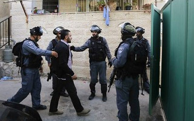 Israel border police confront a Palestinian in the Silwan neighborhood of eastern Jerusalem, where 200 Jews moved into 25 apartments in the middle of the night. (Photo by Sliman Khader/Flash90)