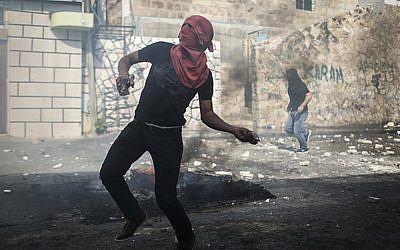 A Palestinian throws a rock at Israeli police during a recent clash that resulted from the attempted assassination of Jewish activist Yehudah Glick and the temporary closing of the Temple Mount. (Photo by Hadas Parush/Flash90)