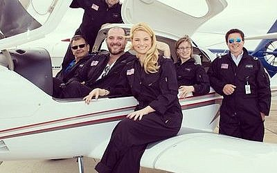 Co-founder Brad Childs (in back, standing) poses with his Pittsburgh Aviation Animal Rescue Team. The group flies to areas in Pennsylvania, Ohio and West Virginia to save animals in distress or danger. (Photo by Bee Schindler)