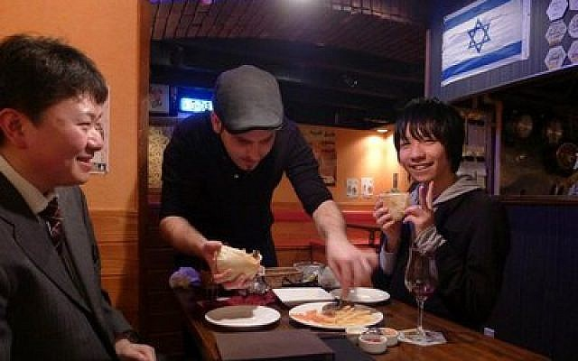 Roy Somech serves patrons at a restaurant he owns in Sendai, Japan.