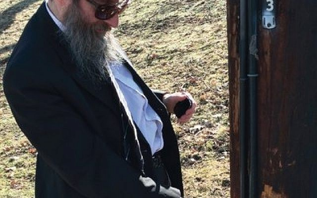 Rabbi Shimon Silver checks an electric pole on which part of the eruv is attached. Silver, spiritual leader of Young Israel of Pittsburgh, is supervisor of the community eruv.  (Photo by Toby Tabachnick)