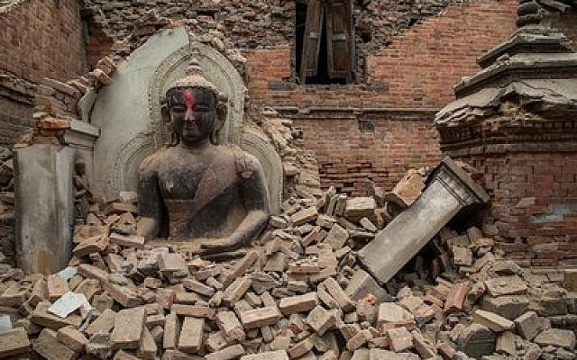 A statue of the Buddha sits among debris from a collapsed temple in Bhaktapur, Nepal.(Photo by Omar Havana/Getty Images)