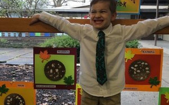 """Maddox Brick, 5, happily shows off his bean-and-seed mosaic. All of the students' creations were """"art for the sake of art."""" (Photos by Hilary Daninhirsch)"""