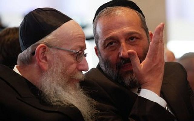 Yaakov Litzman (left), head of United Torah Judaism, and Shas leader Aryeh Deri converse at the opening session of the 20th Israeli parliament in March. (Photo by NatiShohat/Flash90)