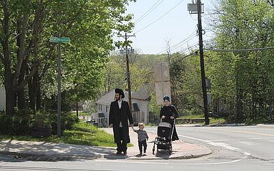Chaim Friedman moved with his wife and two children to Bloomingburg from Williamsburg, Brooklyn. (Photos by Uriel Heilman)  Above right: Twelve Chasidic families live  in the Hickory Street apartments, where Chasidic women gather in the late after- noons to talk.  Right: Strong community opposition in Bloomingburg to the new Chestnut Ridge development has resulted in numerous delays.
