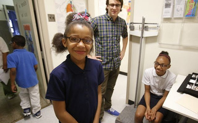Daniel Childs watches as students proudly show off their new glasses. (Photo by Jason Cohen)