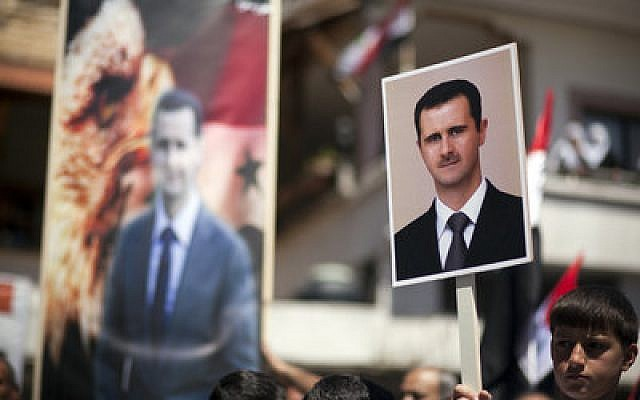 In April 2012, Druze residents of Israel's Golan Heights hold Syrian flags and portraits of Syrian President Bashar al-Assad during a rally in the Druze village of Majdal Shams to mark the Syrian Independence Day. (Photo by Matanya Tausig/Flash90)
