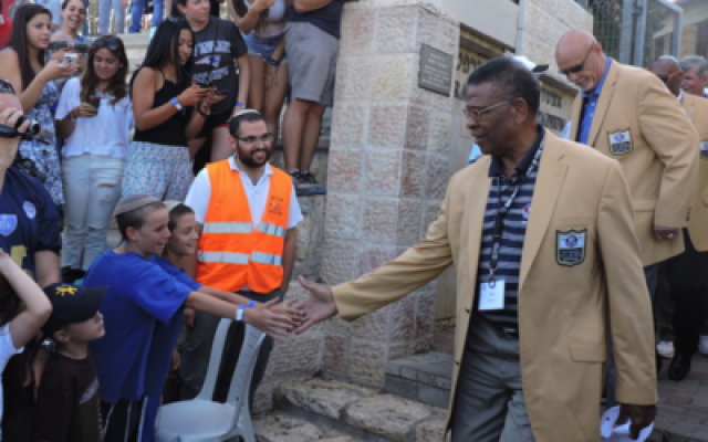 Members of the Pro Football Hall of Fame greet fans last month at Jerusalem's Kraft Stadium. (Photo by Ben Sales)