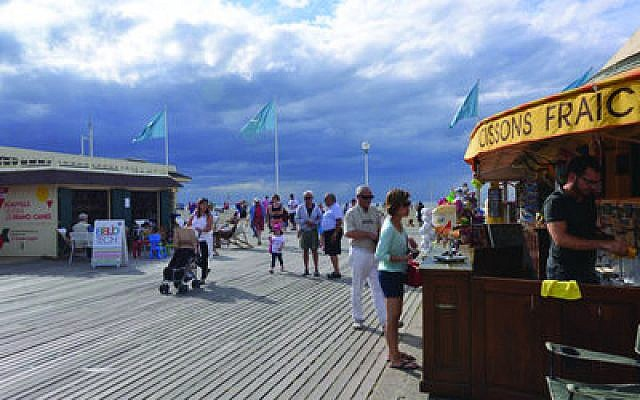 The entrance to the Deauville beach's main boardwalk is a busy place. (Photos by Cnaan Liphshiz)