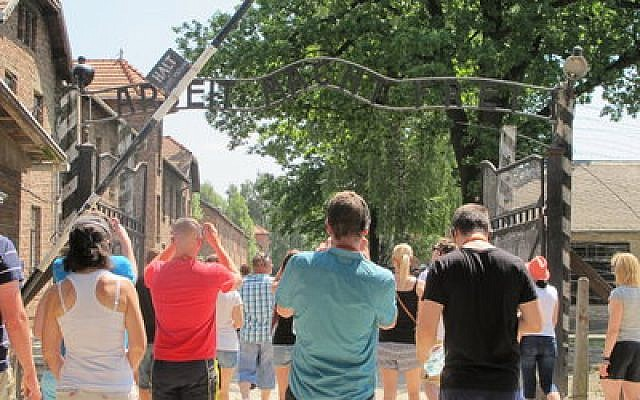 Tourists at Auschwitz photograph the Arbeit Macht Frei gate. (Photo provided by Ruth Ellen Gruber)