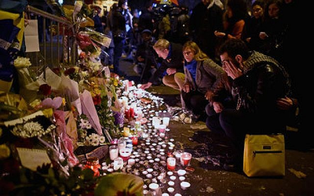 People place flowers and candles near the scene of the Bataclan Concert Hall terrorist attack in Paris. (Photo by Jeff Mitchell/Getty Images)