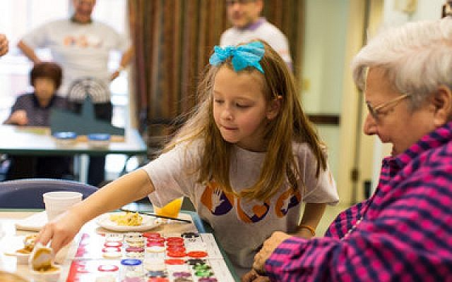 Mitzvah Day activities took volunteers to several senior residences throughout the Pittsburgh region. Here, both players enjoy a game of intergenerational bingo. (Photos by Josh Franzos)