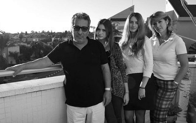 Catherine Berdah poses for a photo with her husband and daughters in their apartment in Raanana, Israel.