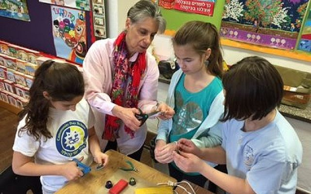 Ronit Schulman's love for jewelry making extends to her fourth- and fifth-grade students at CDS. (Photo by Charlotte Rakaczky)