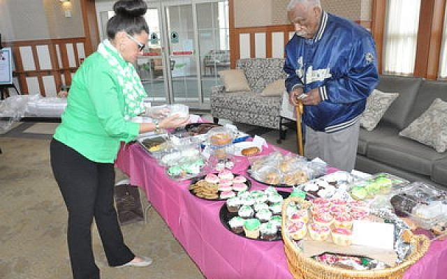 JAA employee Heidi Brown assists a patron during the bake sale.   Photo by Adam Reinherz