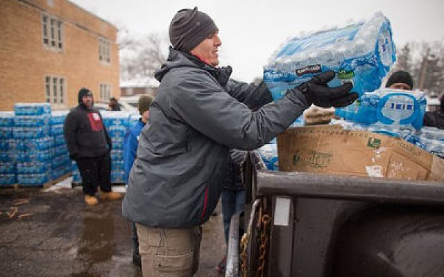 Volunteers load cases of free water into waiting vehicles at a water distribution center in Flint, Mich.  Photo by Geoff Robins/AFP/Getty Images