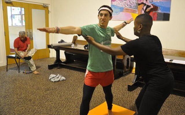 Adam Reinherz receives pose assistance from instructor Felicia Lane Savage.  Photo courtesy of Adam Reinherz