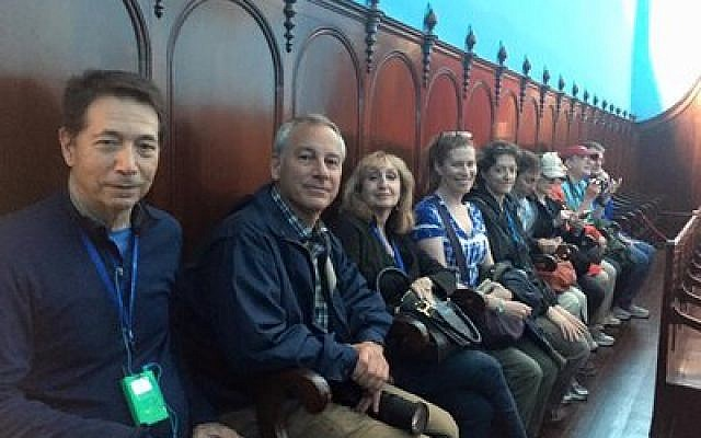 """Tour group members gather for the start of Friday night services in the """"hidden"""" shul, which was built in 1836.  Photo by Yvette Diamond"""