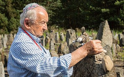 Holocaust survivor Howard Chandler places a stone on a grave in Poland.  Photo provided by Zipora Gur
