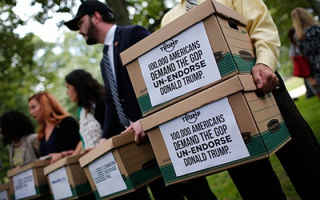 Former members of the military carry boxes with more than 100,000 signatures requesting that Sen. John McCain and other Republican leaders withdraw their endorsement of Republican presidential candidate Donald Trump. Photo by Win McNamee/Getty Images